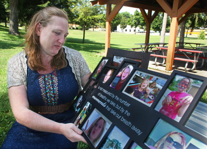 Meredith's moeder Rebecca, met een herdenkingscollage foto's van haar dochter, die bij de begrafenis aan haar werd overhandigd.