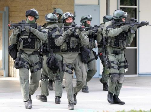 Dit is zo'n zwaar bewapend SWAT-team, met mitrailleurs, kogelvrije vesten, gasmaskers en legerkleding.