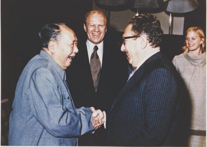 Mao Tze Tung, de historische Chinese partijleider, schudt Kissinger de hand; president Ford kijkt lachend toe.