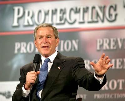 George Bush in zijn rol als beschermende president; achter hem de leus 'Protecting the Homeland'.. Ondertussen zijn de Amerikanen veel van hun fundamentele burgerrechten kwijt; zélf ingeleverd..! Een prachtig motief voor de valse-vlag-aanslagen van 9/11 komt hiermee haarfijn in beeld!