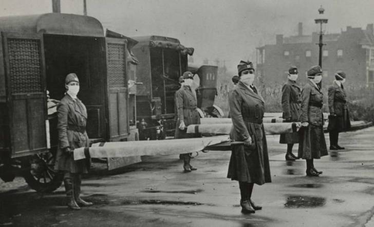 St. Louis Red Cross Motor Corps on duty during the American Influenza epidemic. 1918. mask-wearing women holding stretchers at backs of ambulances. (Photo by: Universal History Archive/UIG via Getty Images)