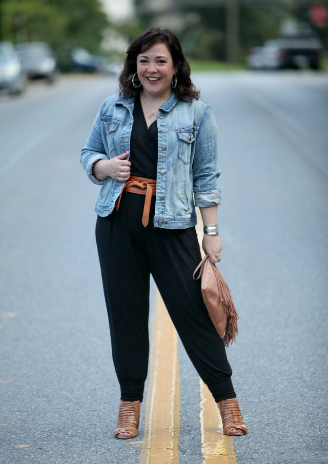 Wardrobe Oxygen featuring a black jersey jumpsuit, denim jacket, and cognac sandals and belt
