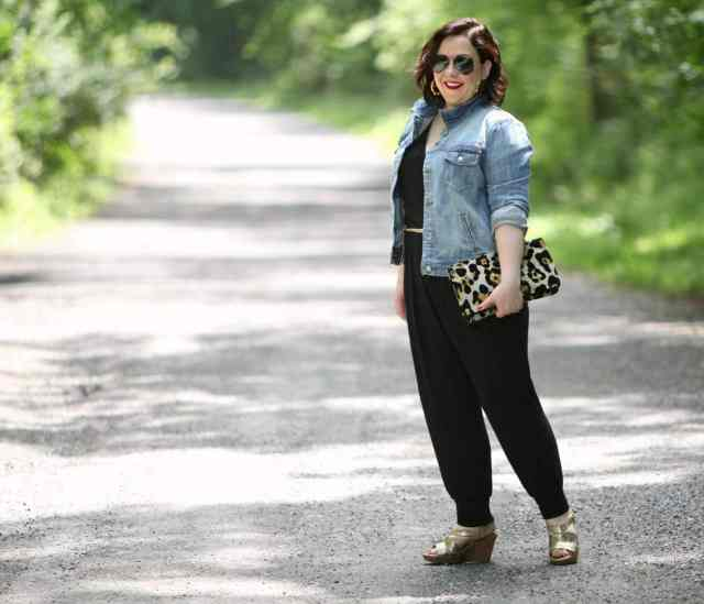 Wardrobe Oxygen wearing a Loveappella jumpsuit, J. Crew Factory denim jacket, and Love,Cortnie clutch bag