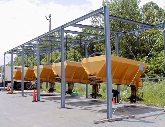 Sand spreaders hang in steel framing in an outdoor lot
