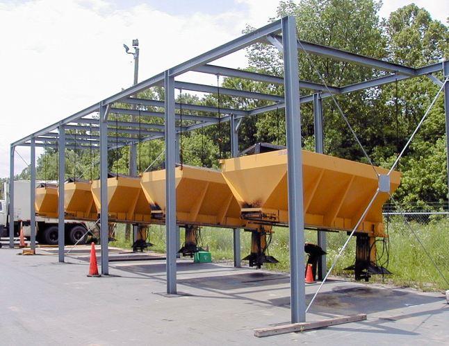 Sand spreaders hang in steel framing in an outdoor lot