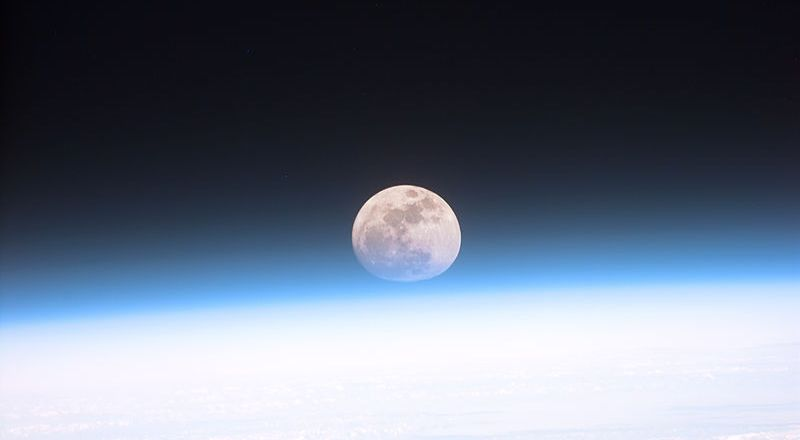 USAF Space Command, full moon partially obscured by earth atmosphere as scene from Space Shuttle Discovery, 21 Dec 1999 (NASA)[800px]