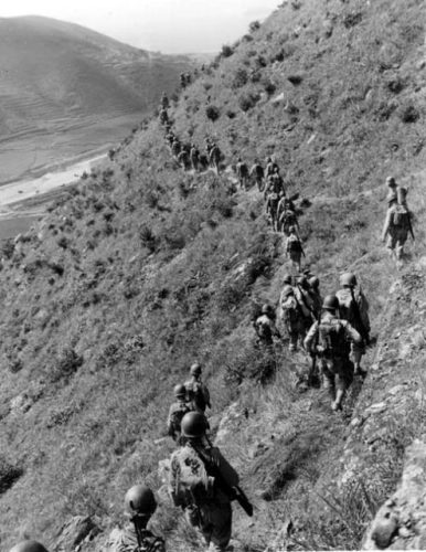 U.S. Marines move out over rugged mountain terrain while closing with hostile North Korean forces.
