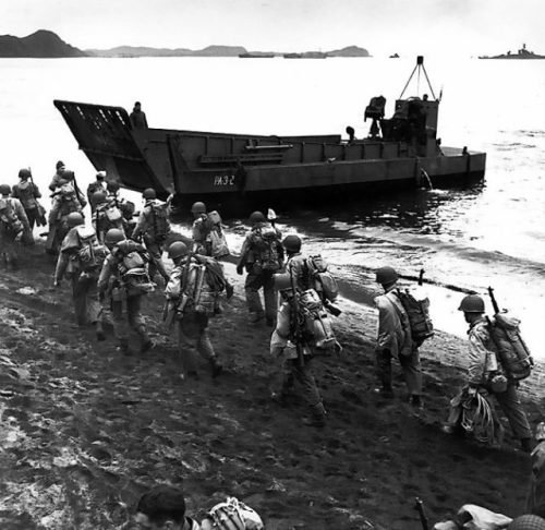 Troops march up the beach at Adak Island, during pre-invasion loading for the Kiska Operation, 13 August 1943. The LCM behind the soldiers is from USS Zeilin (APA-3). USS Pennsylvania (BB-38) is in the far right distance. Note the troops' packs and M1 rifles.