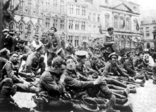 """""""A"""" Company of the 4th Battalion, Royal Fusiliers (City of London Regiment), part of 9th Brigade of 3rd Division, resting in the town square at Mons before entering the line prior to the Battle of Mons. Public Domain, https://commons.wikimedia.org/w/index.php?curid=91487"""