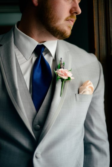 Groom dressed in gray suite, cobalt tie and blush boutonniere