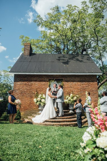 Cottage backdrop for outdoor Kentucky wedding ceremony