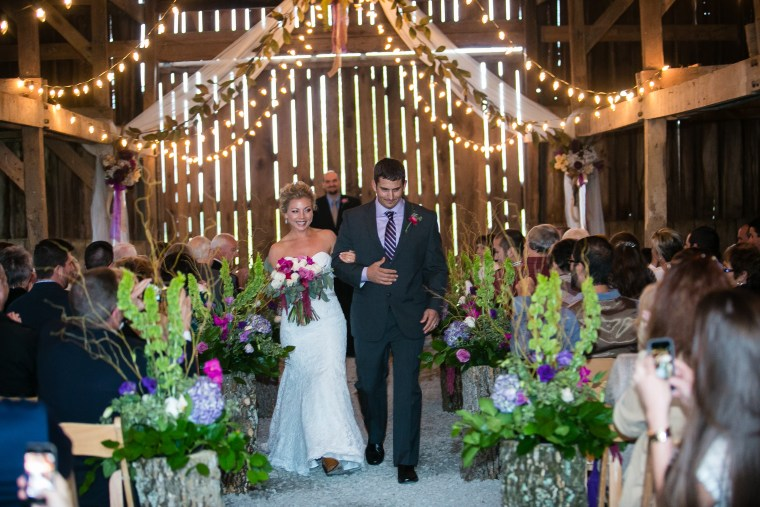 Couple exiting ceremony down aisle lined with stumps and purple florals