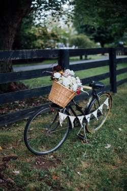 Pennant welcome sign on vintage bike with basket of flowers