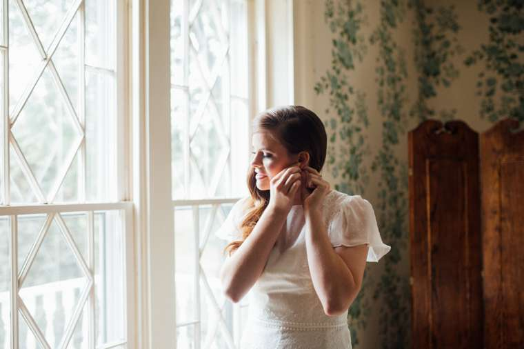 Bride putting in earings in front of large bridal suite windows