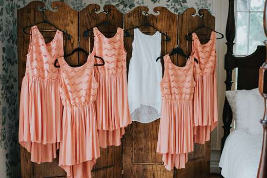 Casual coral bridesmaid dress hanging in the Warrenwood Bridal Suite