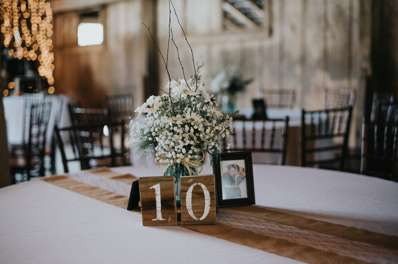Rustic country table setting with wood table numbers and baby'sbreath in blue mason jars at Warrenwood Manor barn