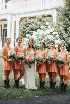 Rustic Country bridal party in cowboy boots and coral dresses