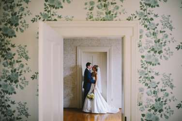 Portrait of Bride and Groom against vintage wallpaper