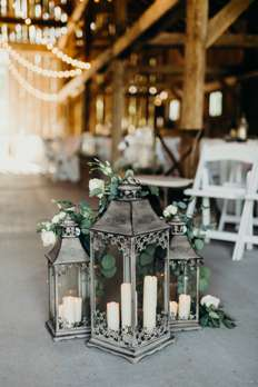 Rustic lanterns with candles and greenery at traditional romantic wedding ceremony