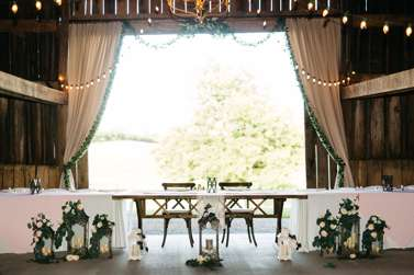 Head table at traditional romantic refined rustic wedding reception
