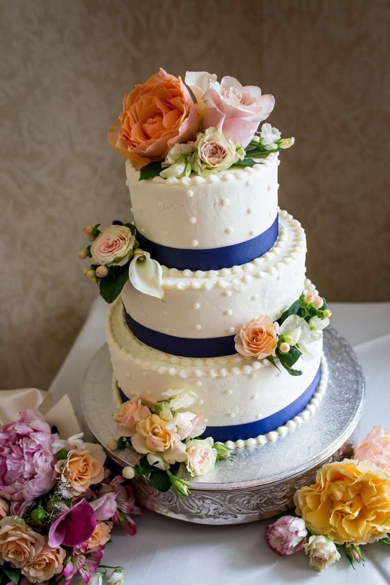 Three-tier ivory polka-dot wedding cake with pink and peach flowers