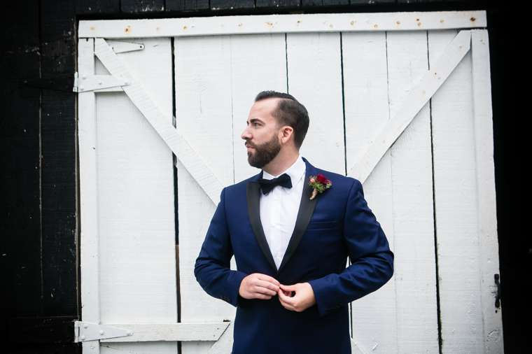 Groom in classy navy & black suite with burgundy boutonniere