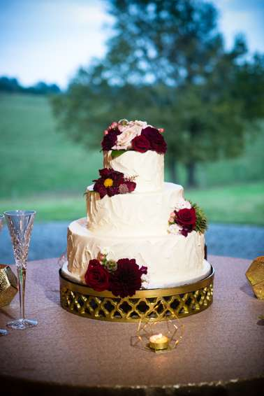 Three-tier white wedding cake with burgundy flowers on gold cake stand