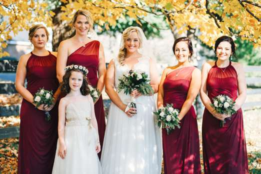 Outdoor fall bridal party portrait with the golden leaves of fall; marsala dresses