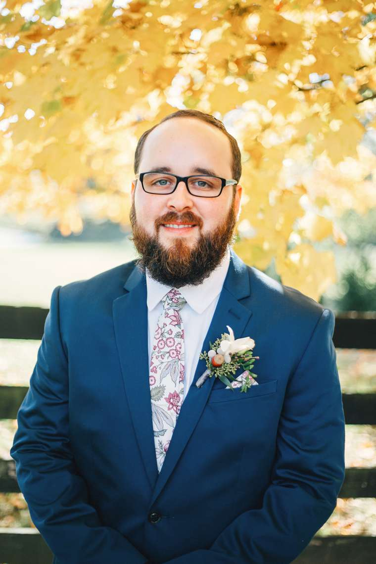 Groom in navy suit with floral tie at fall wedding at Warrenwood Manor