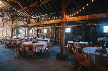 Barn wedding reception with ivory linens and rustic decor
