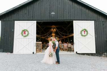 Bride and groom in front of Kentucky wedding barn, destination wedding venue