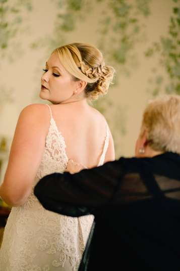 Bride putting on her dress on her wedding day