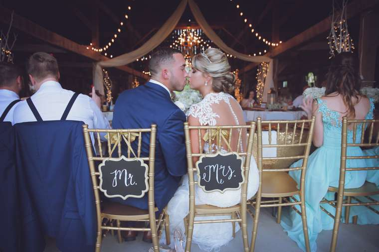 Bride and Groom kiss at vintage glam barn wedding reception