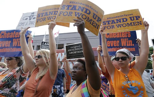 In this July 9, 2013 file photo, opponents and supporters of an abortion bill hold signs near a news conference outside the Texas Capitol, in Austin, Texas. New abortion restrictions passed by the Texas Legislature are unconstitutional and will not take effect as scheduled on Tuesday, a federal judge has ruled. (AP Photo/Eric Gay, File)