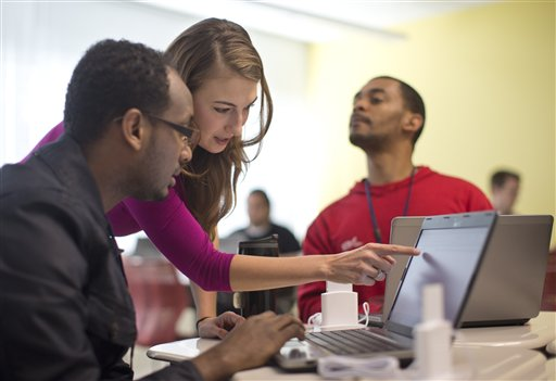 In this Oct. 22, 2013, photo, Kaylin Wainwright, center, works with student Natnael Gebremariam, left, at a computer during a General Educational Development test preparation class at the Sonia Gutierrez Campus of the Carlos Rosario International Public Charter School in Washington. Seated right is student Sibusiso Kunene. Americans who passed part, but not all, of the GED test are rushing to finish it before a new version rolls out in January. About 1 million Americans who took the high school equivalency exam could be affected. GED scores will be wiped out when the new version arrives. Test takers will have to use a computer instead of pencil and paper. And the cost will be significantly higher, at $120. (AP Photo/Carolyn Kaster)