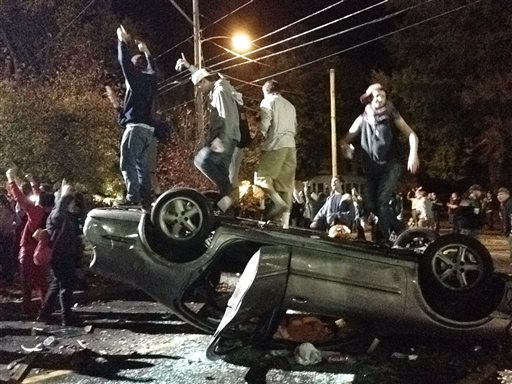 People stand atop an overturned car in Keene, N.H. on Saturday, Oct. 18, 2014, during a night of violent parties that led to destruction, dozens of arrests and multiple injuries, near the city's annual pumpkin festival.  The parties around the school coincided with the annual Keene Pumpkin Festival, where the community tries to set a world record of the largest number of carved and lighted jack-o-lanterns in one place. (AP Photo/The Boston Globe, Jeremy Fox)