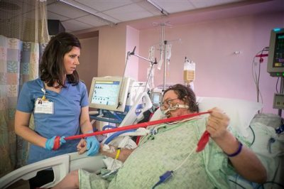 In this photo provided by the Wake Forest Baptist Medical Center, taken March 11, 2015 in the intensive care unit at Wake Forest Baptist Medical Center, physical therapist Katie Kellner helps patient Terry Culler do some exercises and briefly stand despite being hooked to a ventilator. There's increasing evidence that mild exercise may have its place even for the sickest ICU patients, and new animal research suggests it may target both muscles and lungs. (AP Photo/Warren Cameron Dennis III, Wake Forest Baptist Medical Center)