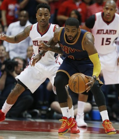Cleveland Cavaliers guard Kyrie Irving (2) moves the ball as Atlanta Hawks guard Jeff Teague (0) looks on during the first half in Game 1 of the Eastern Conference finals of the NBA basketball playoffs, Wednesday, May 20, 2015, in Atlanta. (AP Photo/John Bazemore)