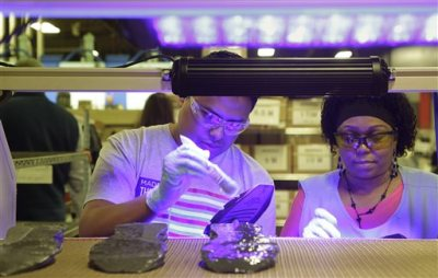 In this photo taken Wednesday July 1, 2015, workers, under ultraviolet light, apply cement to the midsole of the military tested New Balance 950v2 sneaker before the outsole is attached in Boston. New Balance is pressing the Pentagon to buy American-made footwear for the troops instead of sneakers from rival Nike that are made in China. (AP Photo/Stephan Savoia)