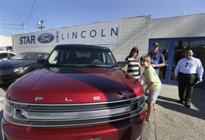 In this Thursday, July 2, 2015, photo, Robert Schemer, his wife, Kelly, and their son Graham, 9, pose next to their newly purchased pre-owned 2013 Ford Flex Limited, at the Star Ford Lincoln dealership in Glendale, Calif. At right is sales consultant Allan Calix. Summer deals and big demand for SUVs and luxury vehicles kept U.S. auto sales strong in July, according to reports released, Monday, Aug. 3, 2015. (AP Photo/Damian Dovarganes)