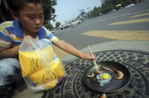 In this photo taken on Wednesday, July 31, 2013, a child demonstrates how raw shrimp and an egg are fried in a pan on a manhole cover on a hot summer day in Jinan in east China's Shandong province. (AP Photo/CHINA OUT)