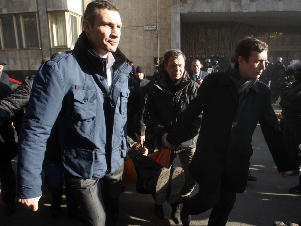 Vitali Klitschko, the UDAR (Punch) party head, helps anti-government protesters carry a wounded man. (Yury Kirnichny / AFP Getty Images)