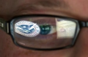 Homeland Security logo reflected in the eyeglasses of a cybersecurity analyst at the agency's secretive cyber defense facility in Idaho. (Mark J. Terrill/AP).
