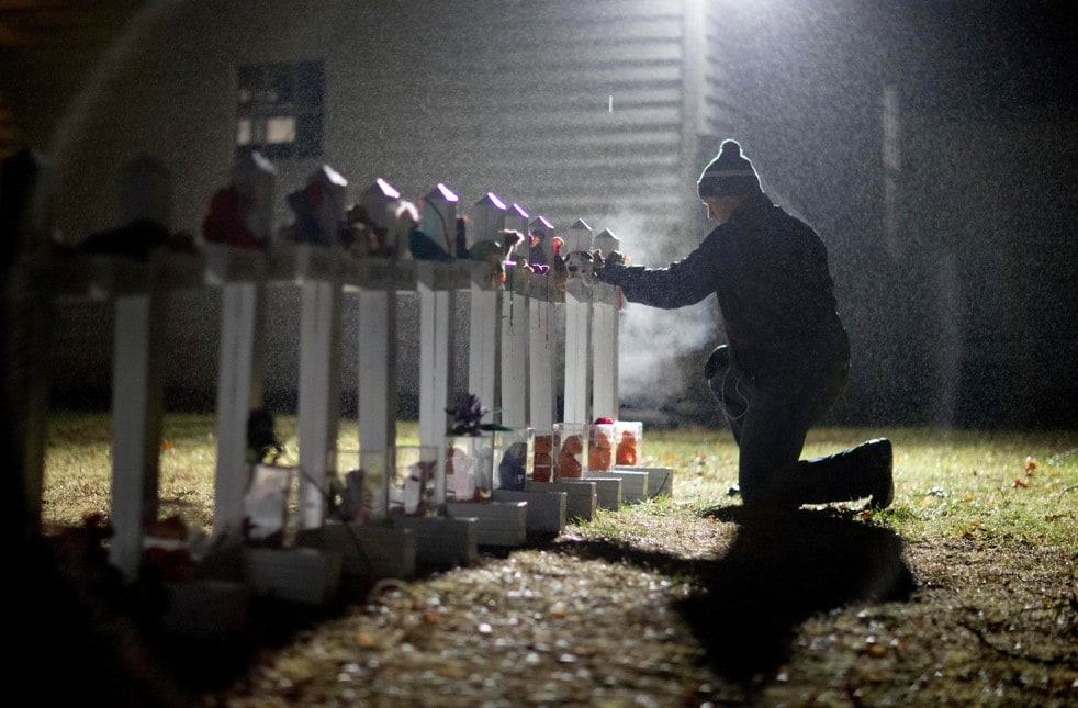 Frank Kulick adjusts a display of wooden crosses—and a Jewish Star of David—on his front lawn representing the victims of the Sandy Hook Elementary School shooting. (David Goldman/AP)