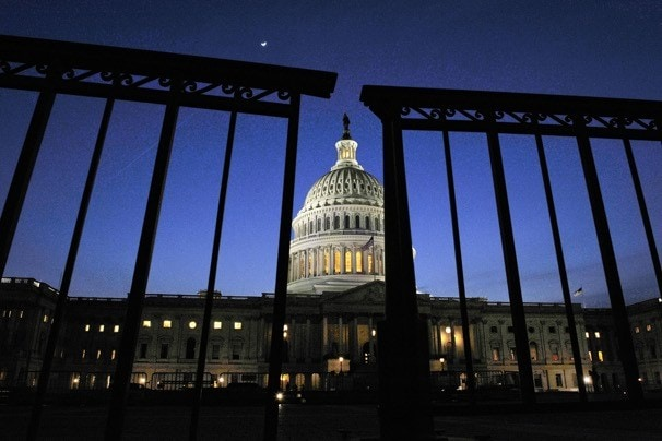 The photograph is cleverly shot to make it look like the gates of the federal government are literally closing. Neat, eh? (The Washington Post)
