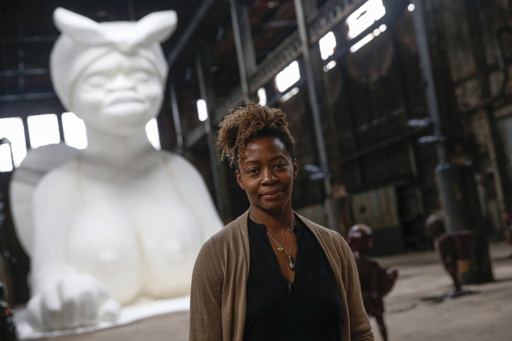 Artist Kara Walker poses in front of her installation 'A Subtlety' sugar-coated with an estimated 40 tons of sugar at the Domino Sugar factory in the Williamsburg section of the borough of Brooklyn in New York May 16, 2014. The sugar-coated sphinx-like figure measures 75.5 feet long, 35.5 feet high and 26 feet wide . REUTERS/Shannon Stapleton  (UNITED STATES - Tags: SOCIETY)