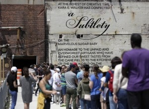 "People cue up to see ""A Subtlety or the Marvelous Sugar Baby,"" by artist Kara Walker, on display inside the former Domino Sugar Refinery, located in the Williamsburg neighborhood of Brooklyn, NY, Saturday, May 17, 2014. Four tons of sugar were used to create the 35-foot-high sphinx-like sculpture.The head of the large sculpture wears a kerchief and slightly exaggerated African features. Her breasts are exposed and her fists are thrust out, described by Walker as both submissive and domineering.  (AP Photo/Richard Drew)"