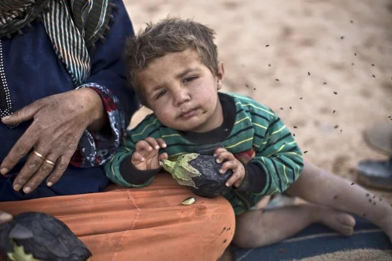A Syrian refugee child at an informal tent settlement near the Syrian border in Jordan in June. (Muhammed Muheisen/Associated Press)
