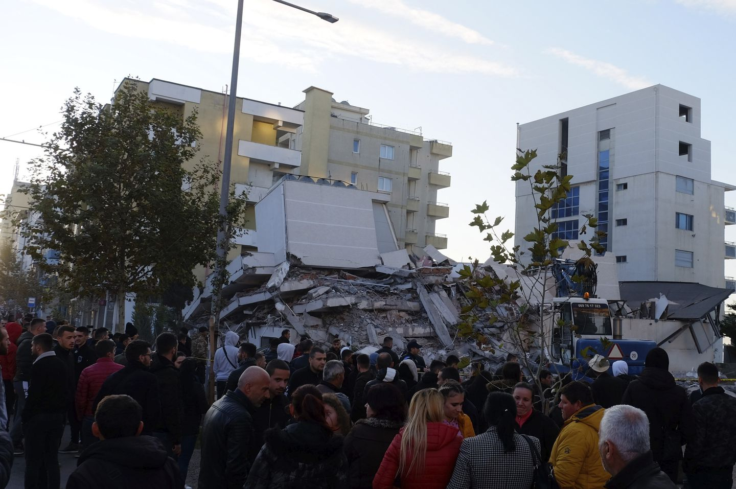 People stand near a damaged building after a magnitude 6.4 earthquake in Durres, western Albania, on Tuesday. (Hektor Pustina/AP)