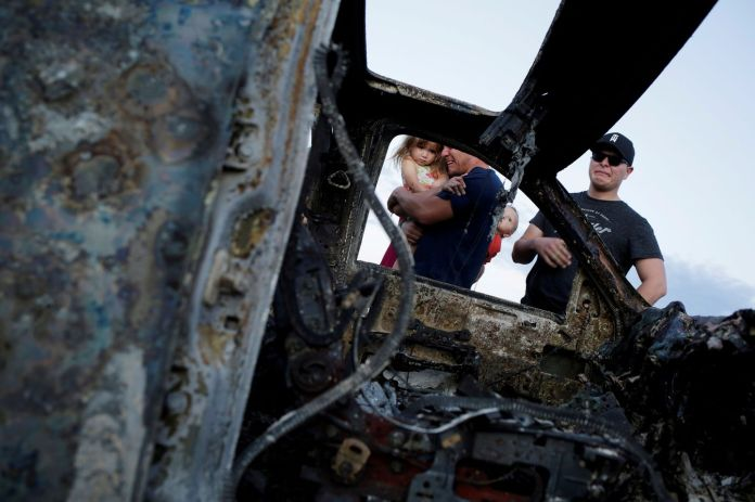 Relatives of the U.S.-Mexican Mormons who were killed react to the burned wreckage of one of the vehicles. (Jose Luis Gonzalez/Reuters)
